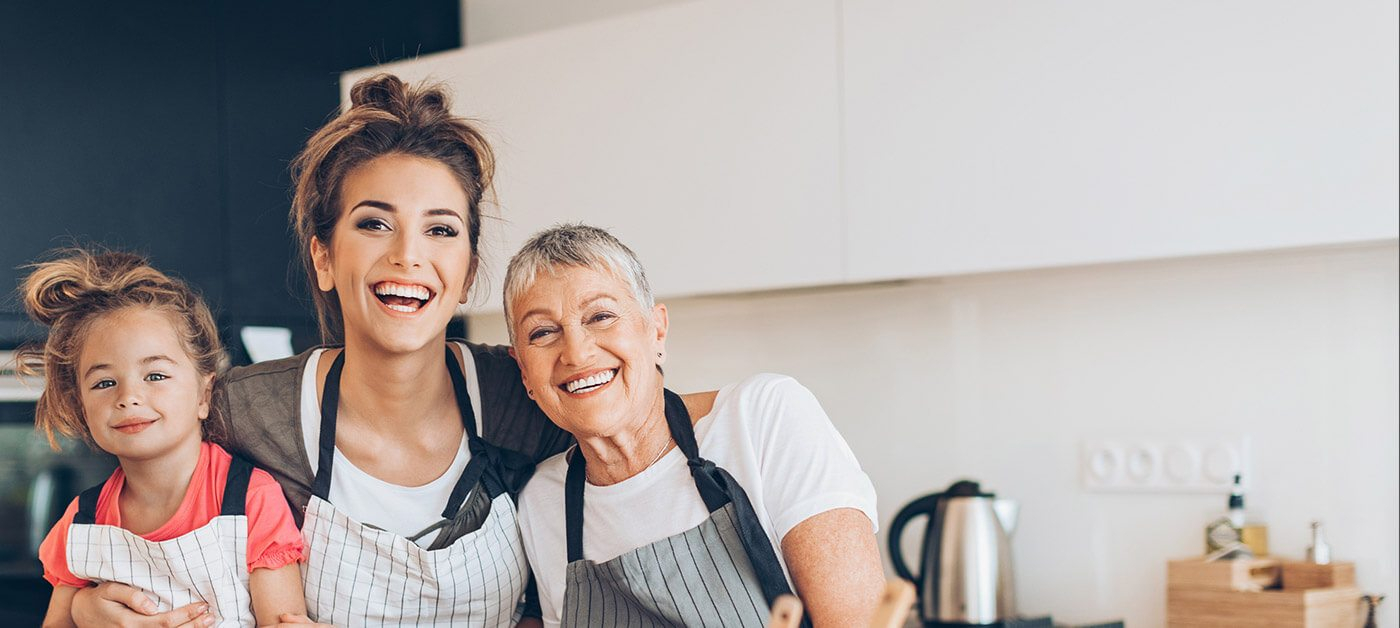Grandmother mother and daughter smiling in aprons