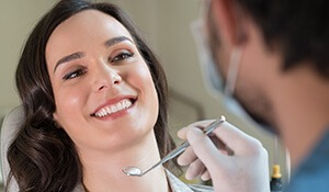 Woman smiling at dentist holding tools