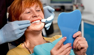 Dentist and smiling woman examine smile in mirror