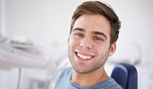 Young man in dental chair smiling