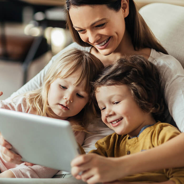 Mother and two smiling kids viewing tablet