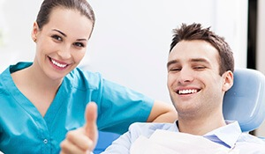 Man gives thumbs up with dental assistant